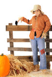 Goofy Teen Scarecrow. An attractive teen scarecrow with a goofy expression.  She's standing by an rustic rail fence with a hay stack, pumpkin and Indian corn Stock Image