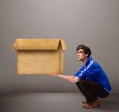 Goog-aussehender Mann, der eine leere braune Pappschachtel hält Stockbild