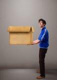 Goog-aussehender Mann, der eine leere braune Pappschachtel hält Stockbilder