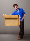 Goog-looking man holding an empty brown cardboard box Royalty Free Stock Photo