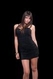 Goog que mira a la muchacha adolescente en un vestido negro sobre fondo negro Foto de archivo