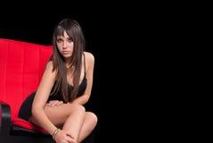 Goog que mira a la muchacha adolescente en un vestido negro sobre fondo negro Fotos de archivo