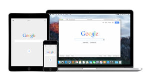 Google app on the Apple iPhone iPad and Apple Macbook Pro Retina. Google app on the Apple iPhone 5s and iPad Air 2 displays and desktop version of Google search stock image