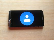Google Contacts app. On smartphone kept on wooden table royalty free stock image