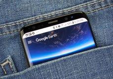 在一手机屏幕的Google Earth在口袋 免版税库存图片