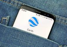 在一手机屏幕的Google Earth在口袋 免版税图库摄影
