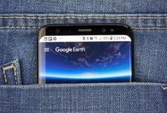在一手机屏幕的Google Earth在口袋 免版税库存照片