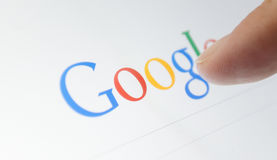 Google with finger on touch screen Stock Images