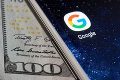 Google icon app on smartphone. New york, USA - April 11, 2018: Google icon app on smartphone close-up on dollar currency background Stock Photo