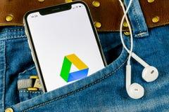 Google kör applikationsymbolen på skärmen för Apple iPhone X i jeansfack Google kör symbolen Google kör applikation samla ihop ko royaltyfri bild
