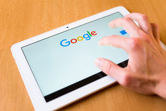 Google. Man's hand use with his fingers tablet. Webpage of Google search engine is on the screen. Google is the biggest searching engine in the world Royalty Free Stock Images