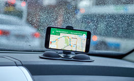 Google Maps application. MONTREAL, CANADA - MARCH 15, 2016 - GPS application Google Maps on Samsung S5 im a car over wet windows background. Google Maps is one stock images