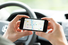 Google Maps navigation on Apple iPhone. KIEV, UKRAINE - MAY 16, 2014: Man in the car planning a route using a Google Maps application on Apple iPhone 5S. Google Stock Photography