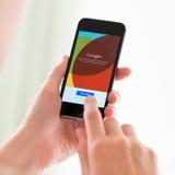 Google más el uso en el iPhone 5S de Apple Foto de archivo