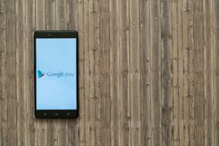Google play logo on smartphone screen on wooden background. Stock Images