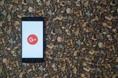 Google plus embleem op smartphone op achtergrond van kleine stenen Stock Afbeeldingen
