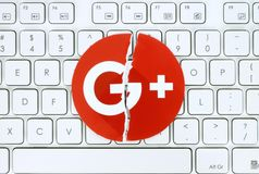 Google plus icon torn and put on white keyboard royalty free stock photo