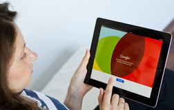 Google Plus. Woman logs in on Google Plus social network on digital tablet Stock Photo