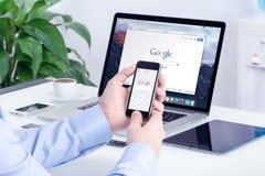 Google procura na tela do iPhone de Apple e exposição de Macbook na pro Imagens de Stock Royalty Free