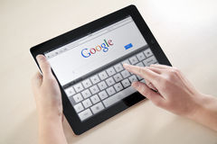 Google Search On Apple iPad2. Woman hands holding and touching on Apple iPad2 with Google search web page on a screen