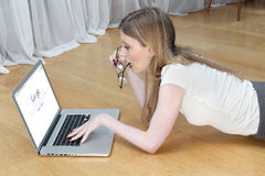 Google search. London, United Kingdom - November 27, 2014: Young girl lying on a floor looking curiously into laptop with Google homepage on computer screen Royalty Free Stock Photography