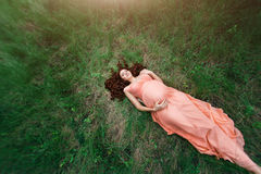 Goorgeous woman laying on green grass field in summer. Attractive mcaucasian girl in peach dress resting on nature. Top Stock Photo