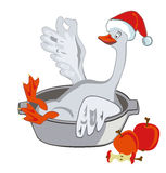Goose with apples in a pot in the cap Santa. Stock Photos