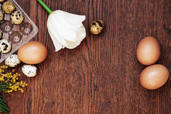 A goose egg, hen egg and a quail egg on a wooden background. Stock Photos