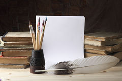 Goose feather and a glass with dirty brushes on the background of old books and sheets of white paper. Retro stylized photo Royalty Free Stock Image