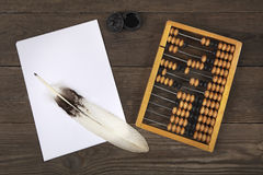 A goose feather lies on a pile of white sheets of paper. Old accounts and a retro inkwell are located side by side on a wooden tab Royalty Free Stock Photography