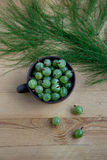 Gooseberries in a clay mug on the wooden background Stock Photos