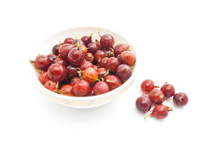 Gooseberries on a dish. Red gooseberries on a dish closeup on white Royalty Free Stock Images