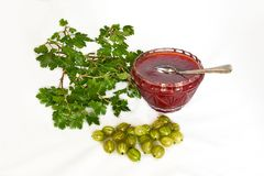 Gooseberries, jam with tea spoon and twig with green leaves Royalty Free Stock Image