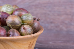 Gooseberries in a wooden bowl Royalty Free Stock Photos
