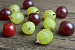 Gooseberry and cherries. On a desk Royalty Free Stock Images