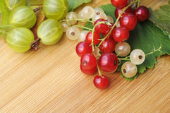 Fruits. Gooseberry, currant, on wooden ground Stock Photos