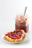 Gooseberry Jam. A slice of bread with butter and gooseberry jam on a small plate and a jam jar with a teaspoon isolated on white background Stock Photo