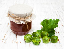 Gooseberry jam. With fresh berries on a wooden background stock photo