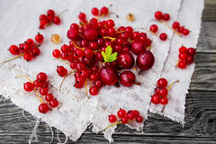 Gooseberry and red currant lie on a homespun napkin Royalty Free Stock Photography