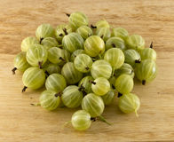 Gooseberry on the table. Pile of gooseberries on the table, which has the texture of wood Stock Photos