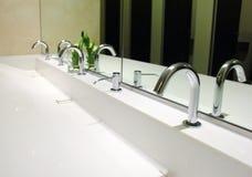 Gootstenen en kranen in toilet royalty-vrije stock foto's