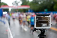 GoPro Camera Shoots Time-Lapse Of Rainy Peachtree Road Race. Atlanta, GA, USA - July 4, 2015:  A GoPro camera mounted on a tripod shoots time-lapse photography Royalty Free Stock Photography