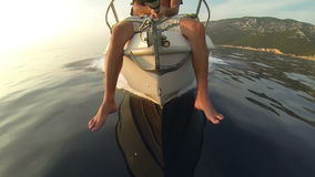 GoPro, slow motion: Man sitting on a speedboat bow while sailing on water stock video footage