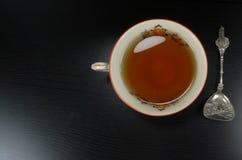 Gorący herbacianej filiżanki biały porselain z łyżką, przy tłem, teatime czarnymi drewnianymi/ obraz stock