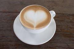 Gorąca biała filiżanka kawy z kierowym kształtem na drewno stole Fotografia Stock