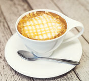 Gorąca cappuccino kawa w białej filiżance na wodd tle, rocznik c Obrazy Royalty Free