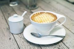 Gorąca cappuccino kawa w białej filiżance na wodd tle, rocznik c Obrazy Stock
