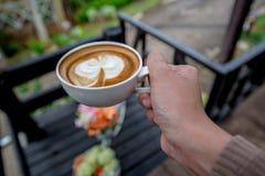 Gorąca cappuccino latte kawa w białym filiżanki mieniu ręką Fotografia Stock