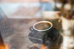gorąca czarna kawa w czarnej filiżance na drewnianym stole przez nadokiennego widoku, zdjęcia stock
