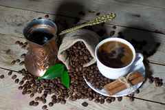 Gorąca Czarna kawa w Kawowym garnku i Białej filiżance z fasolami w Jutowej torbie na Drewnianym stole Cynamonowymi i Kawowymi Fotografia Royalty Free